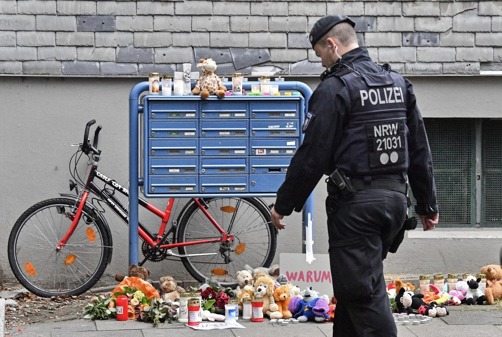 Police passes candles and teddy bears at the entrance of a house where five dead children were found in Solingen, Germany, Friday, Sept. 4, 2020. Poli...