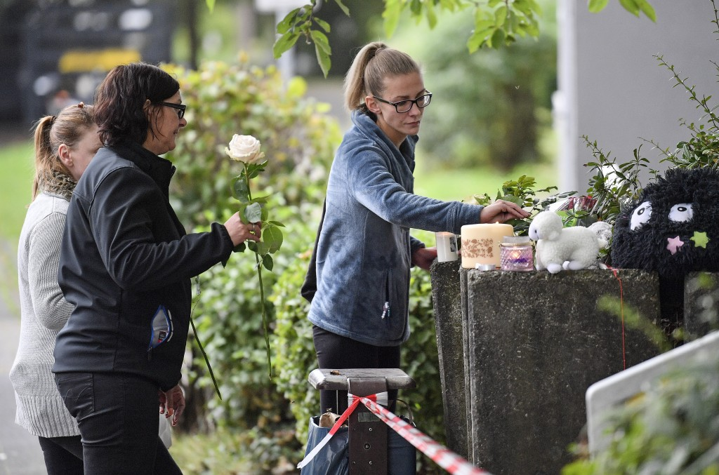 People bring flowers and candles to an apartment building, where five dead children were found in Solingen, Germany, Friday, Sept. 4, 2020. Police say...