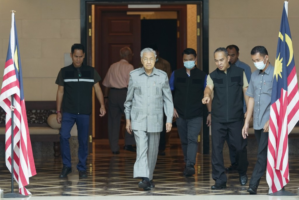 Former Prime Minister Mahathir Mohamad, center, walks out from his office in Kuala Lumpur, Friday, Sept. 4, 2020. Mahathir said Friday that Malaysia's...