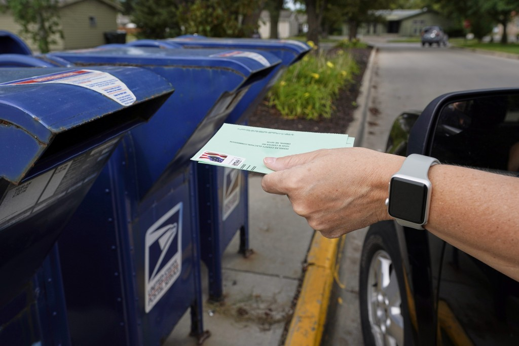 FILE - In this Tuesday, Aug. 18, 2020, file photo, a person drops applications for mail-in-ballots into a mail box in Omaha, Neb. Mail voting is start...