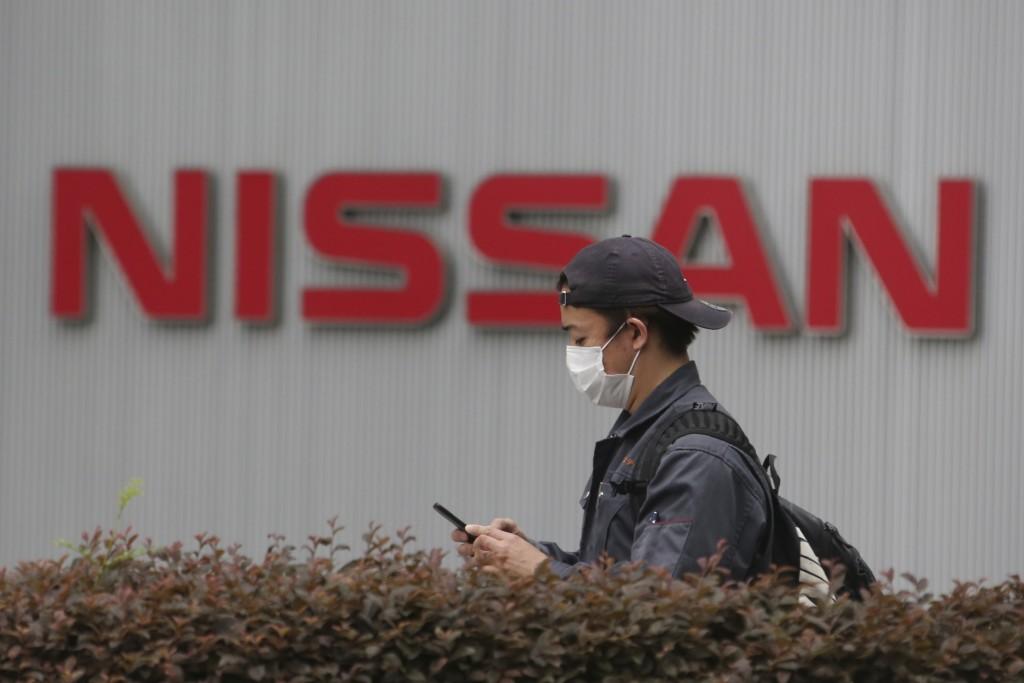 A man walks past the corporate logos at the global headquarters of Nissan Motor Co., Ltd. in Yokohama near Tokyo, Thursday, May 21, 2020. Nissan says ...