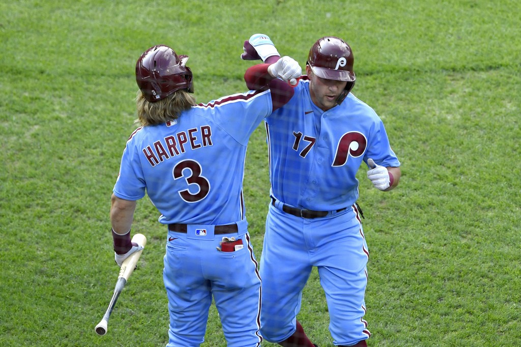 Philadelphia Phillies' Rhys Hoskins, right, celebrates with Bryce Harper (3) after hitting a solo home run off Washington Nationals' Anibal Sanchez du...
