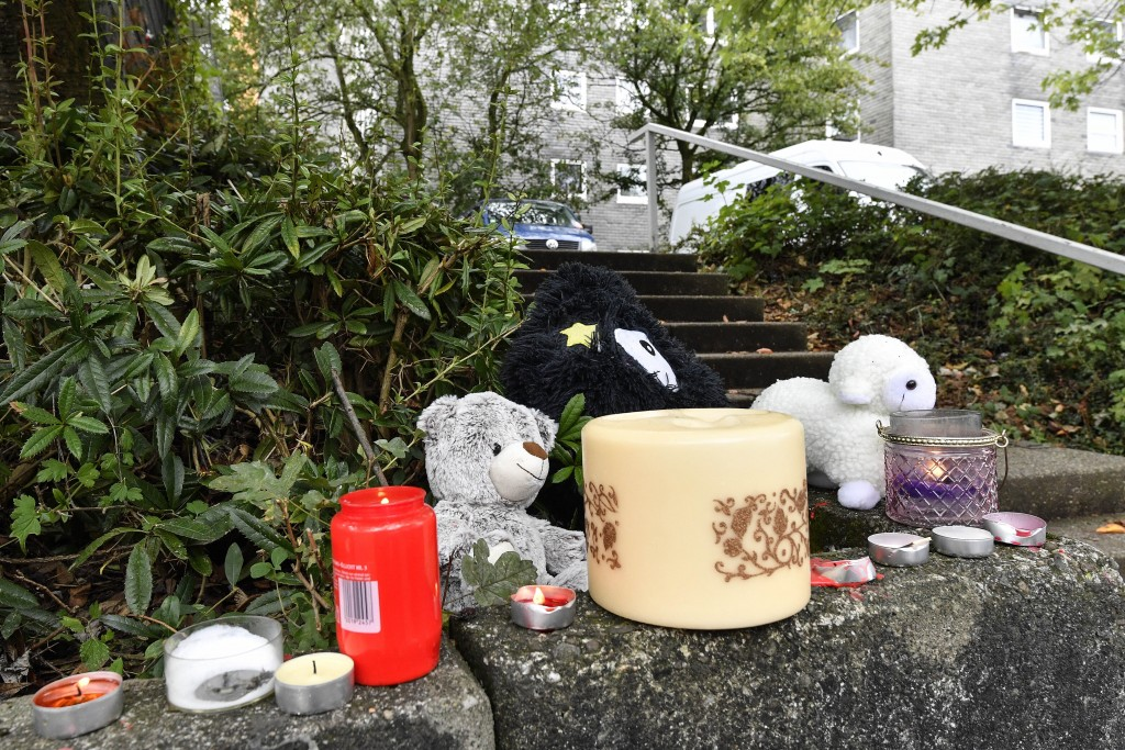 A Teddy bear and candles are set in front of an apartment building, where five dead children were found in Solingen, Germany, Friday, Sept. 4, 2020. P...
