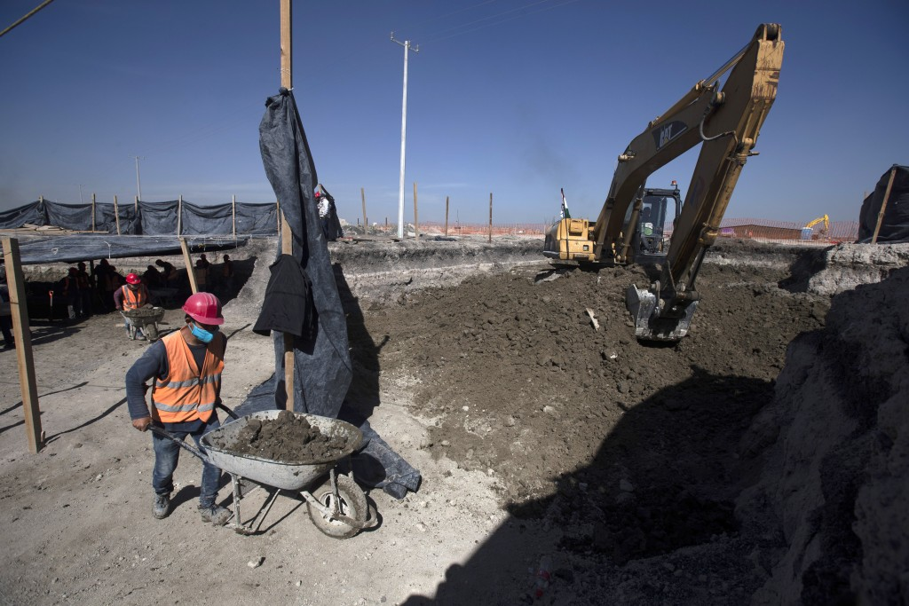 Workers bring out wheelbarrows of dirs as paleontologists work to preserve the skeleton of a mammoth that was discovered at the construction site of M...