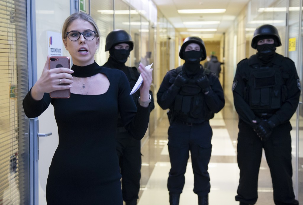 FILE - In this Dec. 26, 2019, file photo, Russian opposition activist Lyubov Sobol speaks on the phone as police stand guard at the Foundation for Fig...