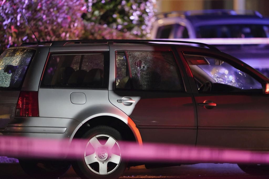 A car with shattered windows and likely bullet holes stands in the area where a man suspected of fatally shooting a supporter of a right-wing group in...