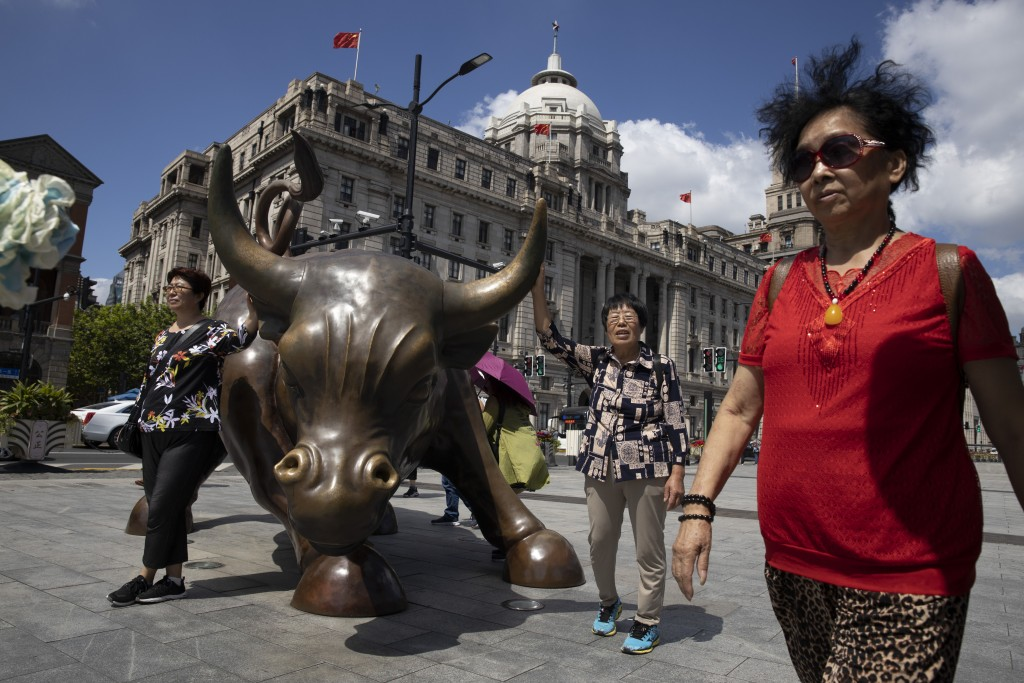 FILE - In this Sept. 20, 2019, file photo, visitors pose for photos near the Bund Bull, a version of the New York Charging Bull sometimes referred to ...
