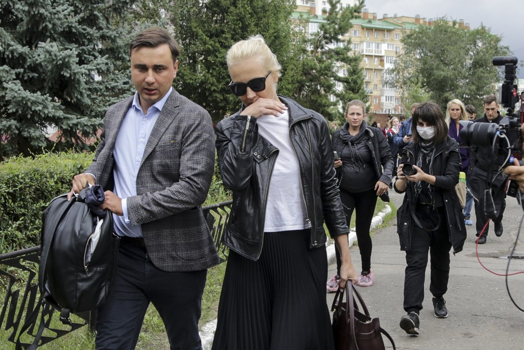 FILE - In this file photo taken on Friday, Aug. 21, 2020, Alexei Navalny's wife Yulia, center, and colleague Ivan Zhdanov, left, arrive at the Omsk Am...