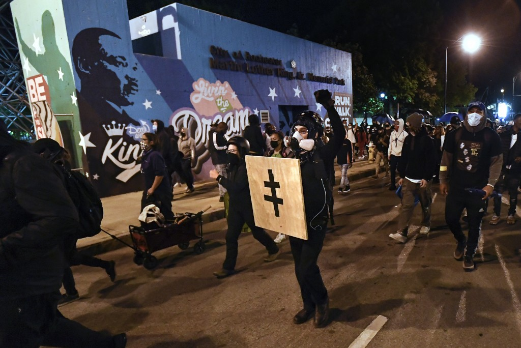 Demonstrators march past Dr. Martin Luther King, Jr. Memorial Park in Rochester, N.Y., Friday, Sept. 4, 2020, during a protest over the death of Danie...