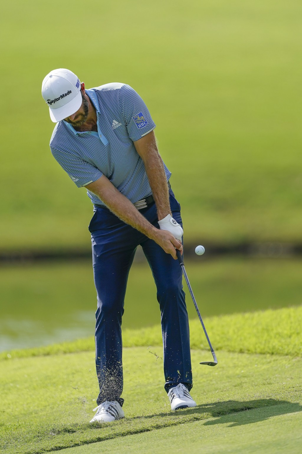 Dustin Johnson chips to the green on the 11th hole during the first round of the Tour Championship golf tournament at East Lake Golf Club in Atlanta, ...