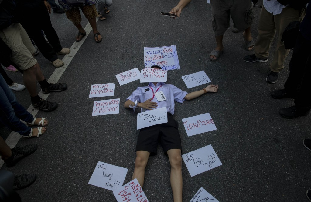 A High school student lies on the ground with placards around him during a protest rally in Bangkok, Thailand, Saturday, Sept. 5, 2020. The student's ...