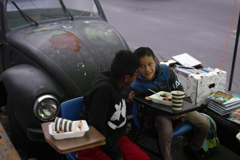 """Brothers Bryan,  right, and Emanuel Quintana, talk as they eat a donated breakfast prior to a history lesson in front of """"Tortillerias La Abuela,"""" or ..."""