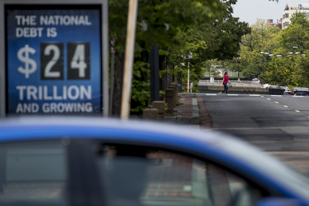 FILE - In this April 29, 2020 file photo, a sign displaying the size of the national debt is displayed along an empty K Street in Washington.  The Con...