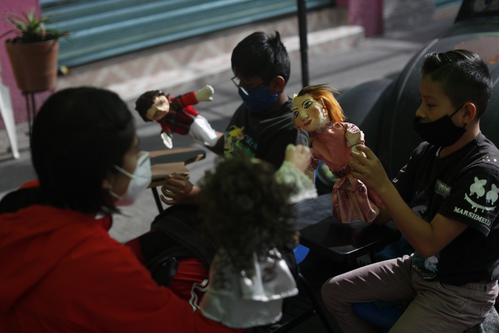 Volunteer Fatima Rodriguez, left, uses puppets to illustrate a history lesson on Spanish colonization and Mexican independence, celebrated in Septembe...