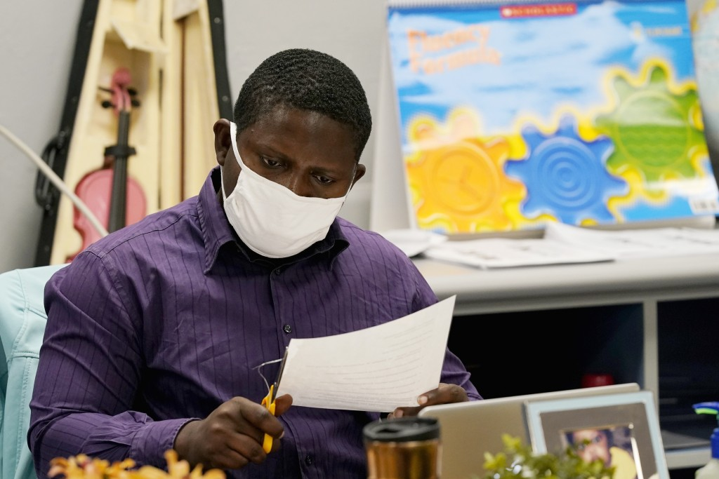 Teaching assistant Samuel Lavi helps out with an online class in the era of remote learning due to the coronavirus at the Valencia Newcomer School, Tu...