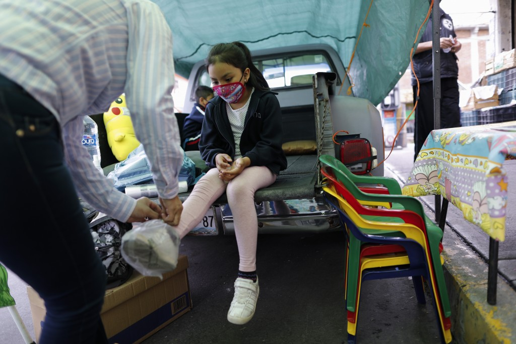 Neighborhood volunteer Rebeca Rodriguez ties plastic bags over the shoes of Paulina Mariano Ortiz who arrives for a lesson in the bed of a pick-up tru...