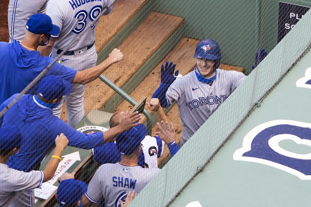 Toronto Blue Jays' Danny Jansen is congratulated by teammates in the dugout after his two-run home run against the Boston Red Sox during the second in...