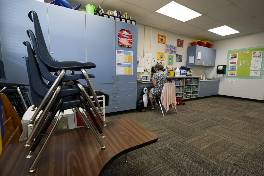 Teaching assistant Susan Jussel works in an empty classroom as she monitors a remote learning class at the Valencia Newcomer School, Tuesday, Sept. 2,...