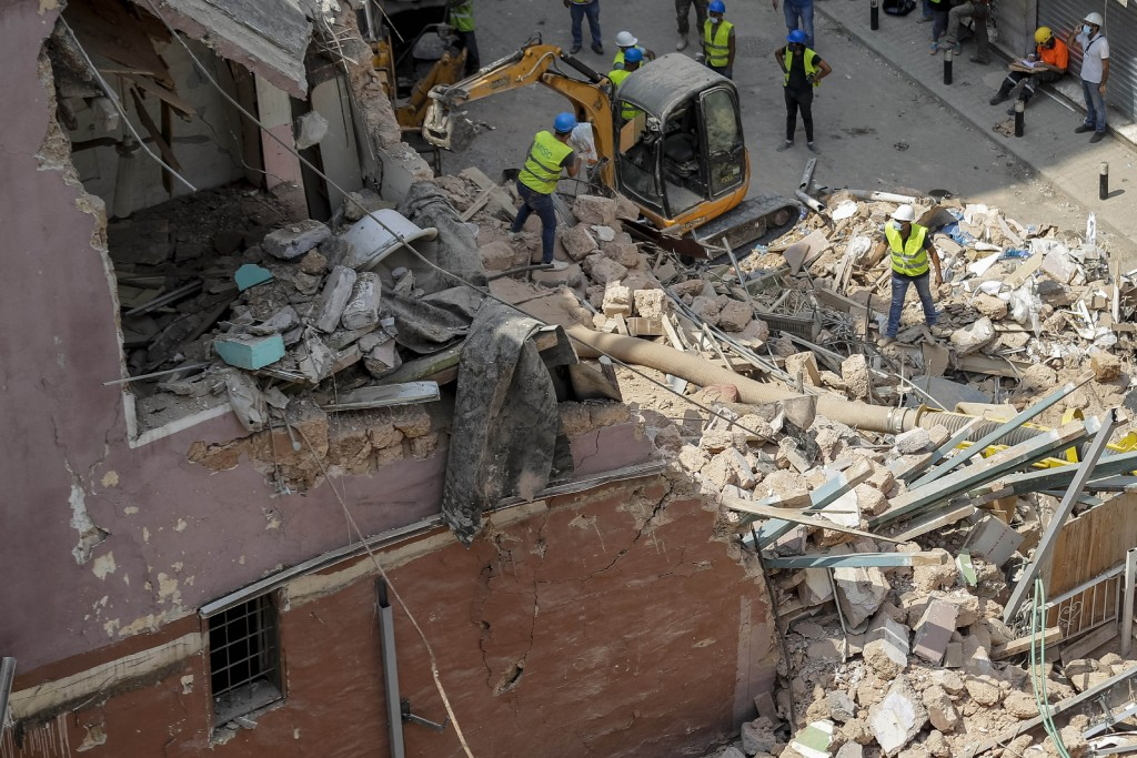 Rescuers search at the site of a collapsed building after getting signals there may be a survivor under the rubble, in Beirut, Lebanon, Saturday, Sept...