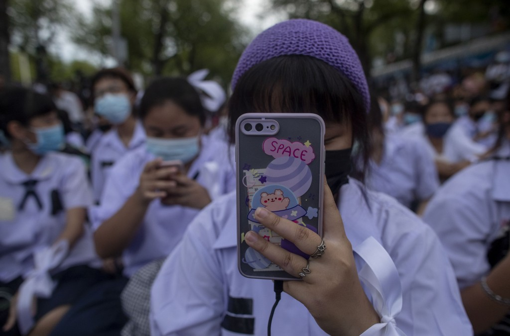 A High school student take pictures as she attends a protest rally in Bangkok, Thailand, Saturday, Sept. 5, 2020. The student's demonstration comes at...