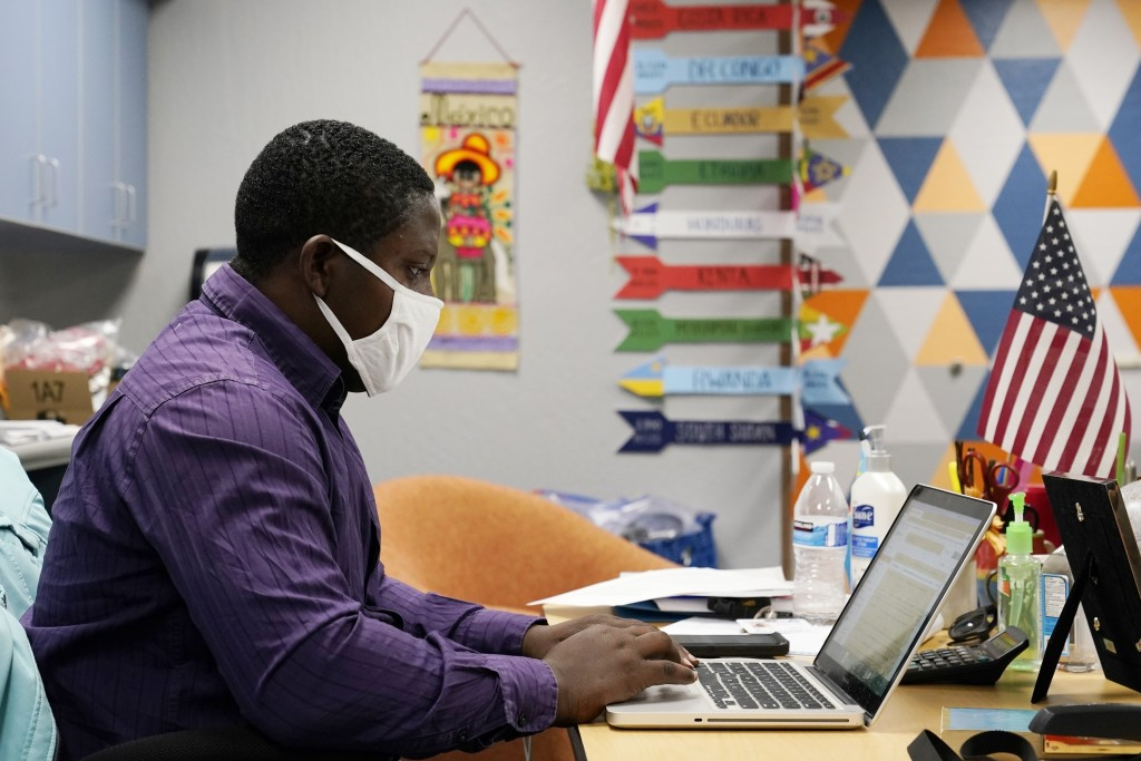 Teaching assistant Samuel Lavi helps out with an online class at the Valencia Newcomer School, Tuesday, Sept. 2, 2020, in Phoenix.  Communicating duri...