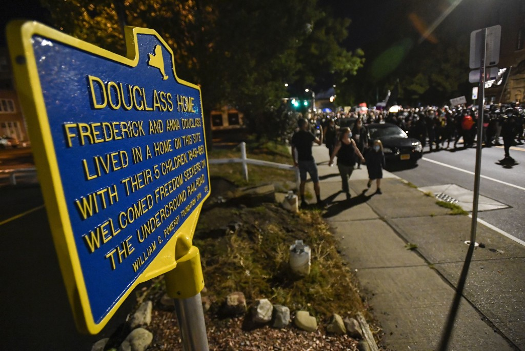 Demonstrators march past the site of abolitionist leader Frederick Douglass' home in Rochester, N.Y., Friday, Sept. 4, 2020, during a protest over the...