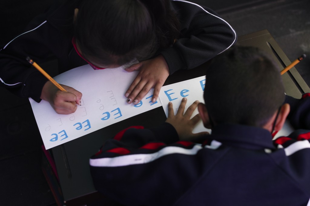 """Siblings Paulina, left, and Axel, practice writing letters in a pick-up truck bed which has been repurposed as an educational space outside the """"Torti..."""