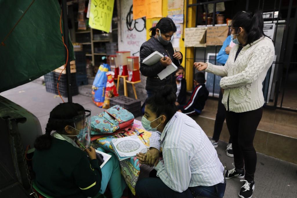 "Dalia Davila Neri, who runs ""Tortillerias La Abuela,"" or ""Granda's Tortilla Shop with her husband, assists student Aide Joselin Hernandez Moreno while..."