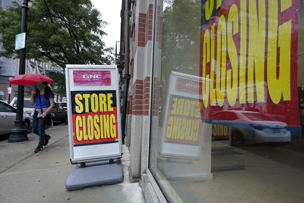 A passer-by walks past a business storefront with store closing signs, Wednesday, Sept. 2, 2020, in Boston. The Congressional Budget Office has warned...