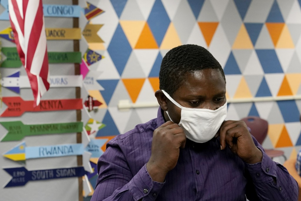 Teaching assistant Samuel Lavi adjusts his face covering at the Valencia Newcomer School, Tuesday, Sept. 2, 2020, in Phoenix.  Communicating during th...
