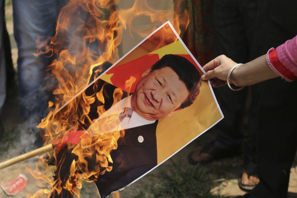 Bharatiya Janata Party activist burns a photograph of Chinese President Xi Jinping.