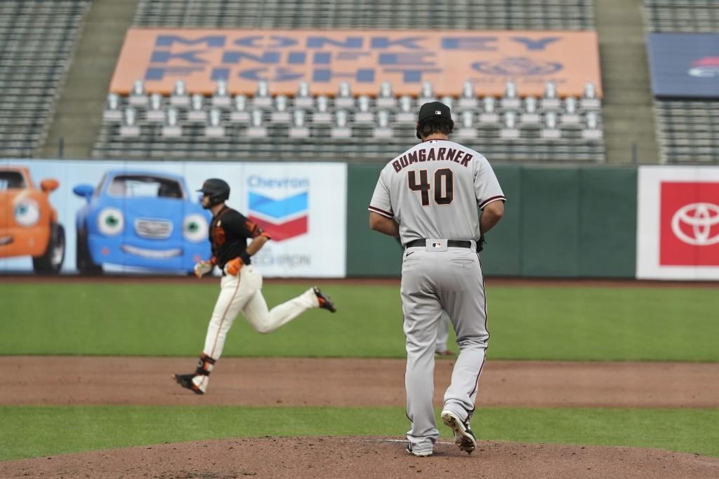 Arizona Diamondbacks starting pitcher Madison Bumgarner walks on the mound after giving up a home run to San Francisco Giants' Evan Longoria, left, du...
