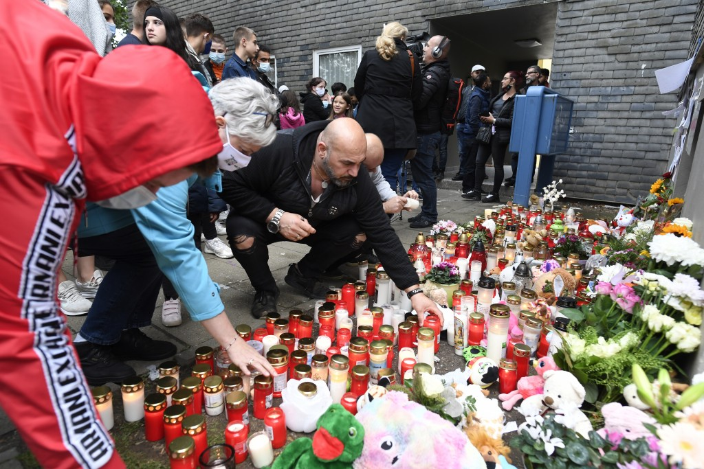 This Saturday, Sept. 5, 2020 taken photo shows neighbour Kasim Ayten and other people lay stuffed animals, flowers and candles in front of the house w...