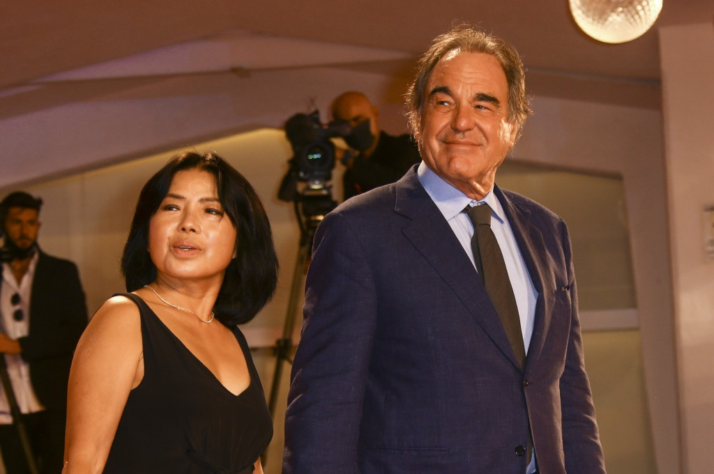 Director Oliver Stone, right, and Sun-jung Jung pose for photographers upon arrival at the un-jung Jung premiere of the film 'Miss Marx' during the 77...