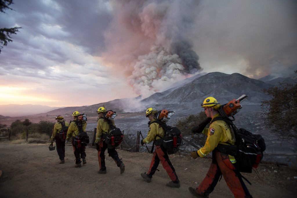 Members of firefighters walk in line during a wildfire in Yucaipa, Calif., Saturday, Sept. 5, 2020. Three fast-spreading California wildfires sent peo...