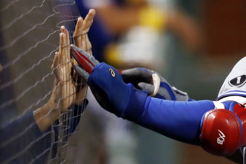 Toronto Blue Jays players press their hands against the netting to celebrate the three-run home run by Vladimir Guerrero Jr., right, during the sixth ...