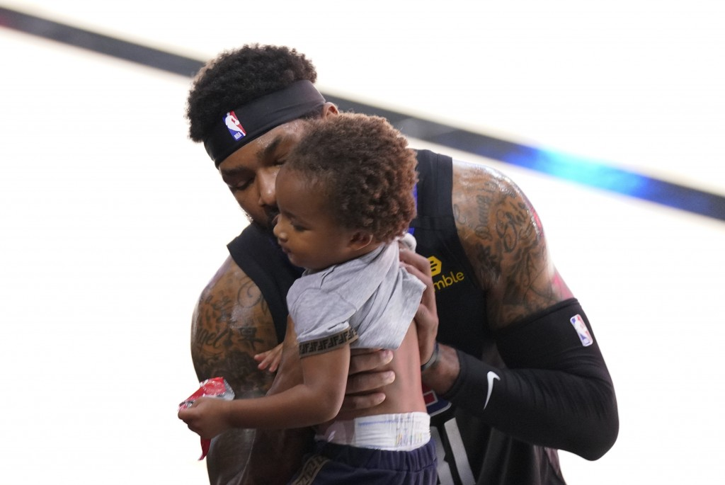 Los Angeles Clippers' Marcus Morris Sr. kisses a baby at the end of the first half of an NBA conference semifinal playoff basketball game against the ...