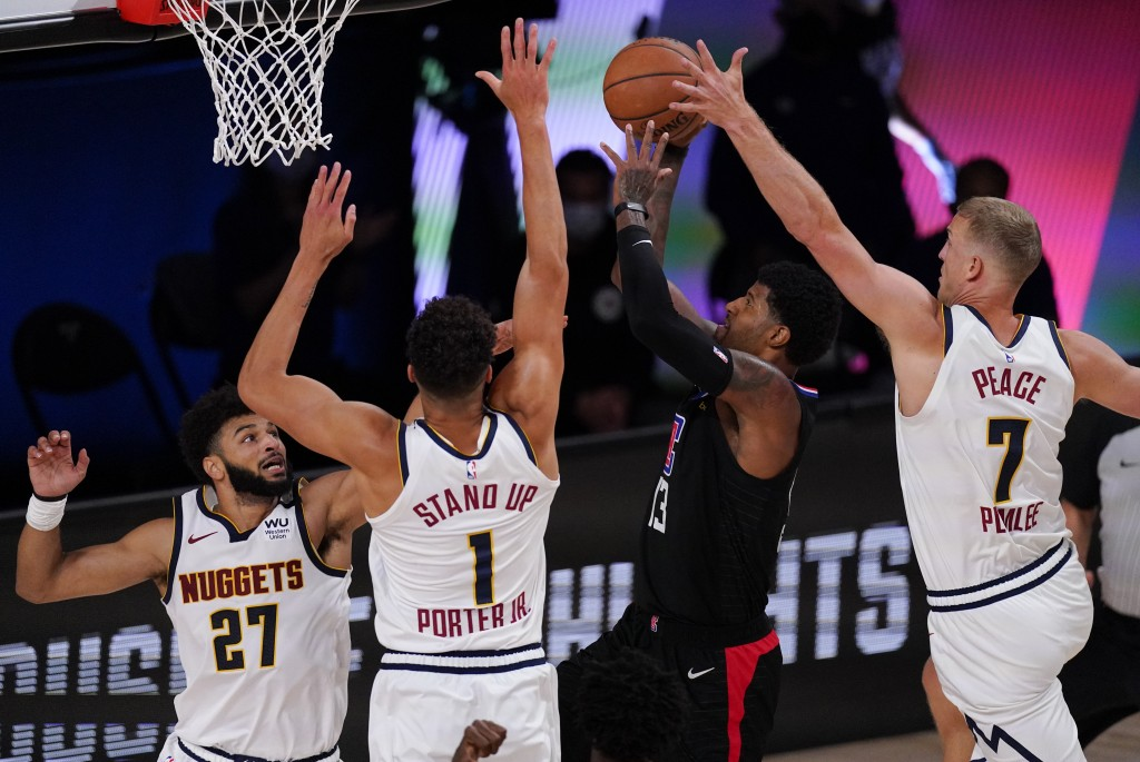 Los Angeles Clippers' Paul George (13) drives to the basket between Denver Nuggets' Jamal Murray (27), Michael Porter Jr. (1) and Mason Plumlee (7) du...