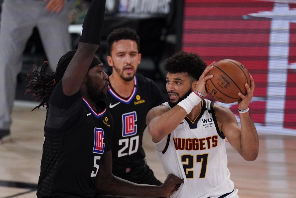 Denver Nuggets' Jamal Murray (27) drives around Los Angeles Clippers' Montrezl Harrell (5) and Landry Shamet (20) during the second half of an NBA con...