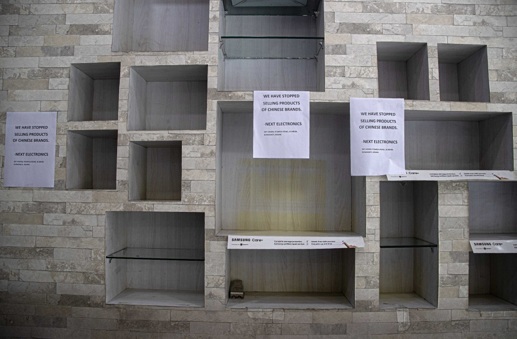 FILE - In this  Thursday, June 18, 2020, file photo, notices hang near empty shelves after the removal of Chinese-made products in an electronic shop ...
