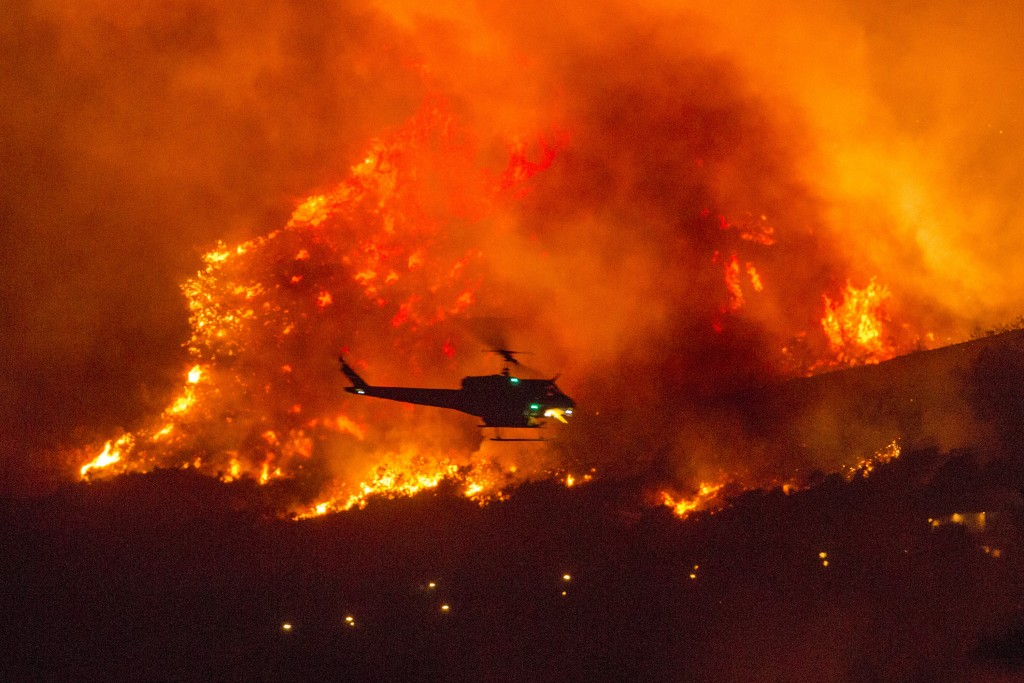A helicopter prepares to drop water at a wildfire in Yucaipa, Calif., Saturday, Sept. 5, 2020. Three fast-spreading California wildfires sent people f...