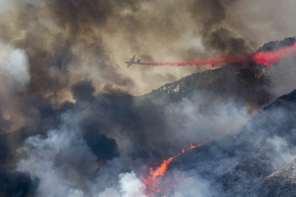 An air tanker drops retardant at a wildfire burns at a hillside in Yucaipa, Calif., Saturday, Sept. 5, 2020. Three fast-spreading wildfires sent peopl...