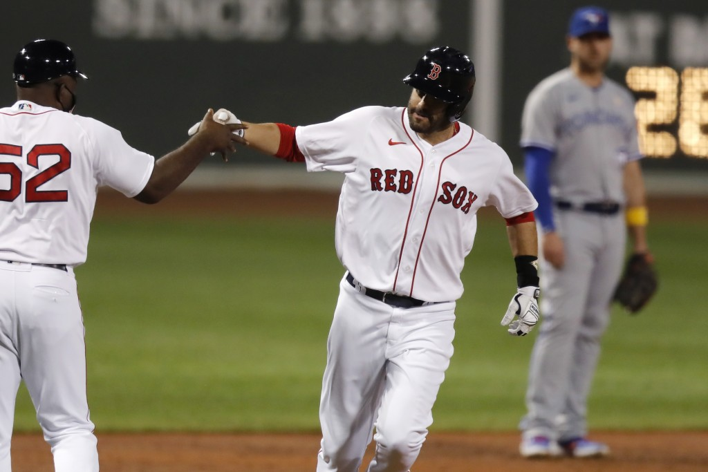 Boston Red Sox's J.D. Martinez rounds third base on his solo home run as Toronto Blue Jays' Travis Shaw, right, watches during the second inning of a ...