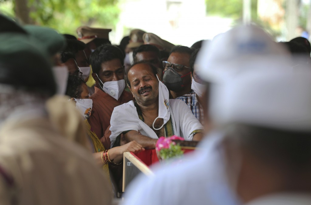 FILE - In this Thursday, June 18, 2020, file photo, B. Upender weeps by the coffin of his son Colonel B. Santosh Babu, who was among the twenty Indian...