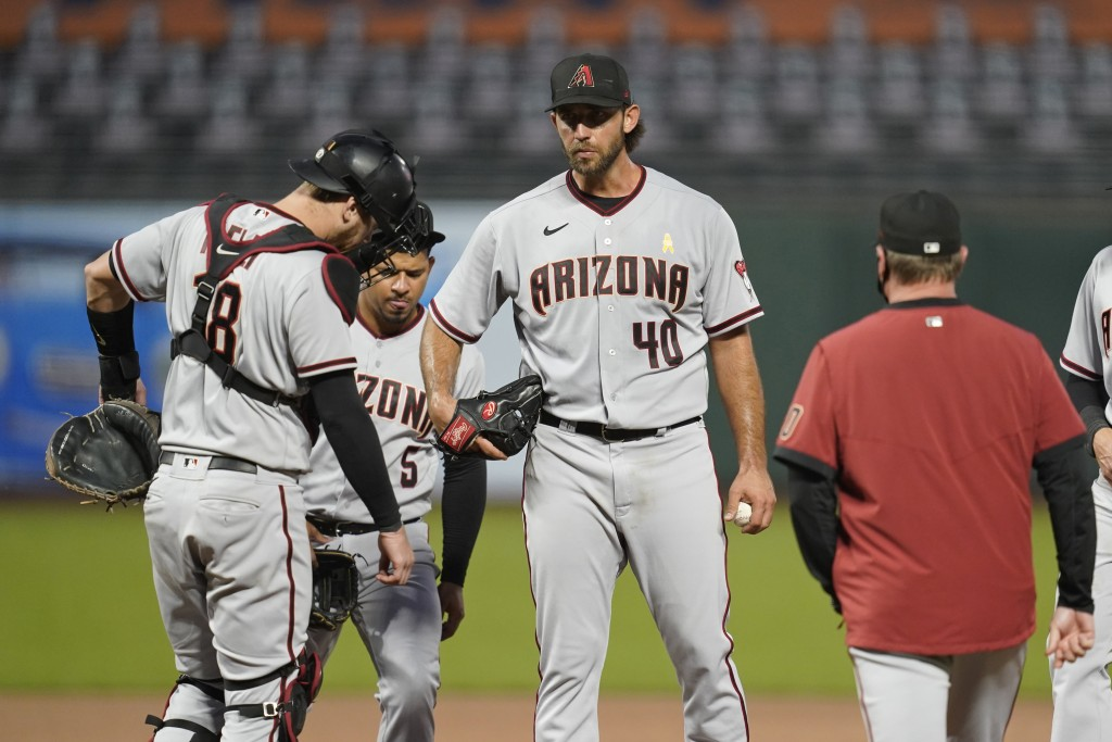 Arizona Diamondbacks starting pitcher Madison Bumgarner (40) stands on the mound and waits for a conference with pitching coach Matt Herges as catcher...