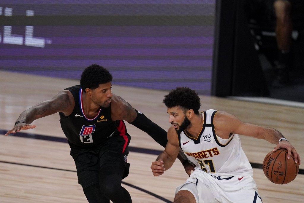Denver Nuggets' Jamal Murray (27) drives past Los Angeles Clippers' Paul George (13) during the second half of an NBA conference semifinal playoff bas...
