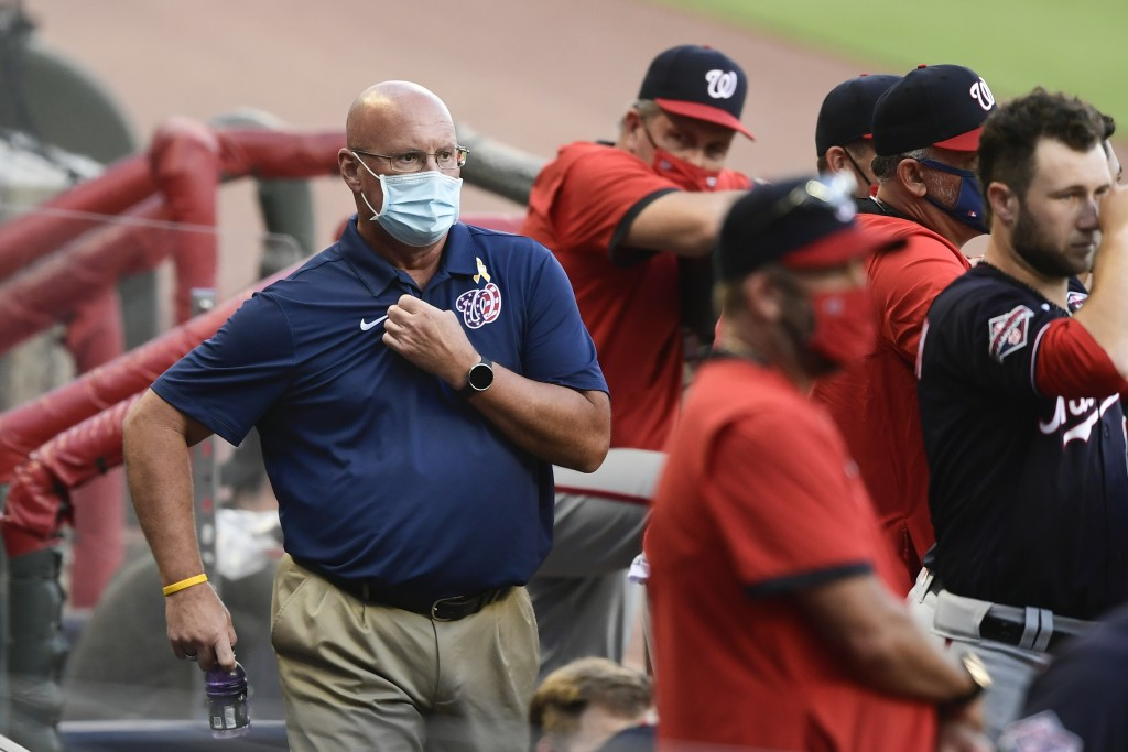 Washington Nationals general manager Mike Rizzo, left, looks on from the dugout as a baseball game against the Atlanta Braves gets underway, Saturday,...