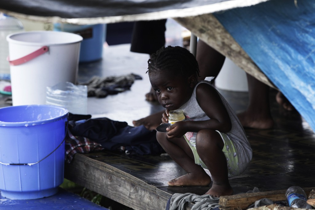 A migrant child peeks out from under a tent at a migrant camp amid the new coronavirus pandemic, in Lajas Blancas, Darien province, Panama, Saturday, ...