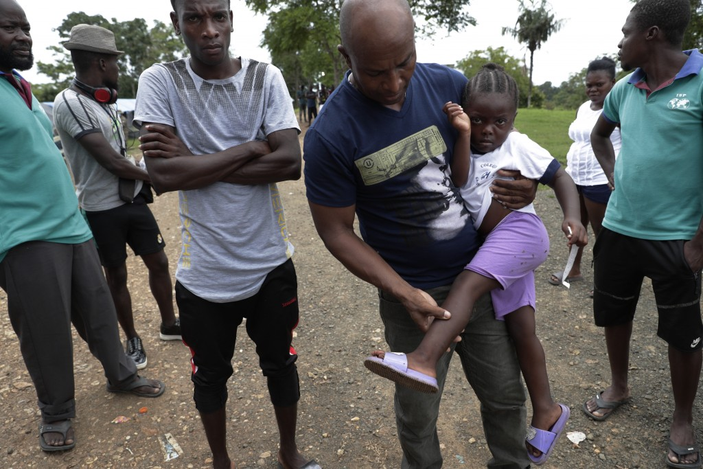 Haitian migrant Jean Bernadeau show insects bites on a girl's legs, at a migrant camp amid the new coronavirus pandemic in Lajas Blancas, Darien provi...