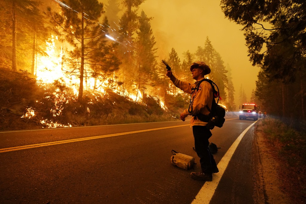 Gabe Huck, a member of a San Benito Monterey Cal Fire crew, fires flares to ignite a controlled burn as he fights the Creek Fire along state Highway 1...